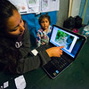 Roxa Rojas Vera-Pinto browsing through the camera trap photos to see what has been caught on photo. Patanmarca, Peru. Here a spectacled bear i seen on the screen. © Daniel Rosengren
