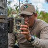 Eddy Torres checking a camera trap. Pampas del Heath, Bahuaja Sonene NP, Peru. © Daniel Rosengren / FZS