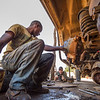 A mechanic fixing a car at the FZS garage in North Luangwa, Zambia. Nils Elbert is filming him. © Daniel Rosengren