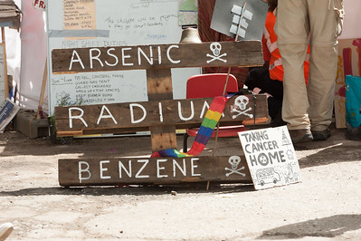 People protest against Fracking in Balcombe over worries of water pollution caused by Caurdrilla drilling operation. Sign displays water pollution from arsenic, radium, benzene,