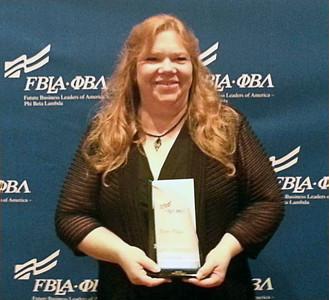Lynda Seneff poses with award