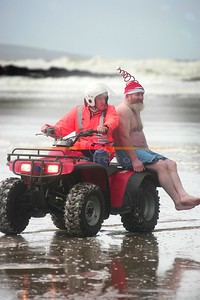 THe Santa Rescue.... A member of Ballybunion Sea and Cliff Rescue comes to teh aid of Michael O Keeffe Lixnaw AKA Santa after he pulled a muscle on the run to the water on the Christmas DAy swim in Ballybunion. Photo Brendan Landy