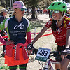 Blanco Lobato-Roberts, JV Rocky Mountain is greeted by Coach Jenny Gerow at finish.