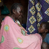 "Nyota Mutwale Pascalina, 54<br /> (Grandmother looking after 8-year old Kyonda Maope)<br /> Among the sea of small straw huts, sits a rather non-descript hut where a woman sits with a little girl and three other women chatting and eating.  Nyota arrived to Katanika in May with her six of her seven children.  <br /> ""In my home village, Katibili, I used to be a farmer,"" she said.  ""Until the attacks came.""<br /> Last November, Nyota had to flee very suddenly with her children when her village got attacked.  They left with nothing but the clothes on their backs and Nyota left her husband behind.  She and her children and granddaughter walked on foot for days, sheltering in churches in a nearby village.  <br /> ""I left my husband behind the day I ran from my village.  I still have no idea where he is.""<br /> Then, one of her older daughters got sick.  With no money or access to good health facilities, her daughter eventually passed away.  She then became the caretaker of her 8-year old granddaughter, Maope.<br /> Eventually Nyota was able to find a place of her own for rent—rent she would pay through tilling the land of strangers.  But when the money was no longer enough to pay the rent and feed her family, she had to leave.  It was then that she found her way to Katanika.<br /> ""The new people in Kantanika tell me that Katibili is not secure up to now,"" she lamented. ""If there was peace, I would go home and start again.""<br /> An upsurge in violence in several parts of DR Congo in 2015, has left over 1.7 million people to flee their homes this year alone; that's over 5,500 people per day. This week, DR Congo was declared the worst affected by displacement in the world by the global analysts, IDMC. Tanganyika province, is one of the hotspots of the current crisis.<br /> <br /> Despite the UN putting the world on notice about Congo's crisis, little has changed since October. Money has only trickled in to help the 13 million people in need. Today the country is the second lowest funded of the world's largest crises - less than half of the US$812 million aid appeal is funded. <br /> <br /> The violence has prevented many families from accessing land and maintaining their livelihoods. 7.7 million people are severely food insecure, up 30 per cent in a year. Lack of access to clean water has led to a cholera outbreak that has killed some 600 people.<br /> <br /> The Katanika Displacement Settlement is located just outside the centre of Kalemie town.  The settlement houses nearly 9,500 families (just under 70,000 individuals) most of whom fled violent interethnic clashes in Kalemie Territory.  The majority of people living in Katanika arrived in two waves—the first wave in January 2017 and the second in May.  Very little assistance has been given to people living in Katanika due to administrative blockades and lack of funding for local and international NGOs to adequately address needs.  <br /> Food is scarce in the settlement and the only means to earn money is through menial jobs like chopping wood, transporting bags of sand and working in the fields.  The average amount a displaced person earns for this kind of work is 625 Congolese francs or less than US 0.40 cents a day.<br /> Health needs are rife in the settlement.  Many are suffering from malaria, malnutrition, severe diarrhea, dysentery and cholera.  There have also been reports of hypertension and strokes.  There is no aid for pregnant women or women who give birth.  People who get severely ill and need professional medical attention rarely have the means to go to hospitals outside of the settlement<br /> Children in the settlement are not able to access quality education.  In certain parts of the camp, locals have set up makeshift schools (under trees) and one or two NGOs have set up an emergency education programs for about 400 students.  <br /> Almost all people in Katanika have listed, cash, food, clean water, clothes, healthcare and education as their most crucial needs.<br /> Most people in the camp have said they would like to return to their home villages, but not until they are certain there is peace and only if they can receive assistance to start their lives again. <br /> <br />  An upsurge in violence in several parts of DR Congo in 2015, has left over 1.7 million people to flee their homes this year alone; that's over 5,500 people per day. This week the DR Congo was declared the worst affected by displacement in the world by the global analysts, IDMC. Tanganyika province, is one of the hotspots of the current crisis.<br /> <br /> Despite the UN putting the world on notice about Congo's crisis, little has changed since October. Money has only trickled in to help the 13 million people in need. Today the country is the second lowest funded of the world's largest crises - less than half of the US$812 million aid appeal is funded. <br /> <br /> The violence has prevented many families from accessing land and maintaining their livelihoods. 7.7 million people are severely food insecure, up 30 per cent in a year. Lack of access to clean water has led to a cholera outbreak that has killed some 600 people.<br /> <br /> Photos: NRC/Christian Jepsen"