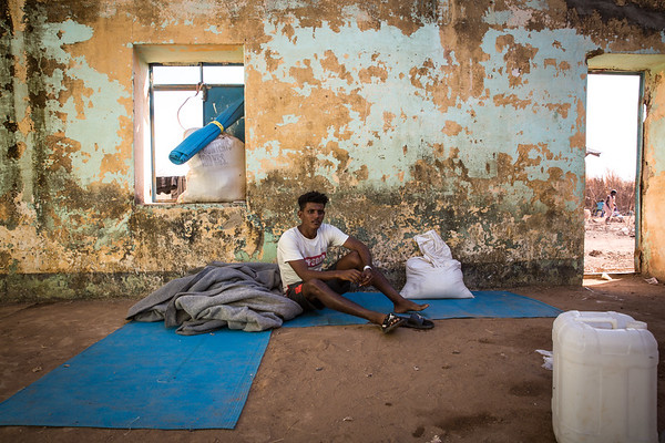 """Ashenafi, 19 years old,  fled alone from Ethiopia and has not heard from his family since then. He arrived two weeks ago and lives with 14 other people in what used to be a school from when the camp was last open and hosted Ethiopian refugees during the big famine in the 1980s. The roof is partly missing and the living conditions are dire. <br /> <br /> """"I saw they were killing young men, so I fled. Here I feel safe,"""" he tells NRC. <br /> <br /> Photo: Ingebjørg Kårstad/NRC"""