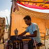 Ebrahim, 24 years old, has set up a small tailor shop in Um Rakuba camp. The only one so far in the camp. Business is good as many refugees had their clothes thorn during the long days of travel. He shares the income with the owner of the sewing machine.<br /> <br /> Photo: Ingebjørg Kårstad/NRC