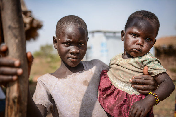 "Nadia holding her little sister Salama (2). They fled from Yei in South Sudan in October 2016 together with their family and are currently living in Bidibidi in Uganda. <br /> <br /> Quotes from Nadia: ""It is okay staying here. We are free and allowed to walk around and I do not feel afraid. It is safe here."" <br /> <br /> Bidibidi settlement in northern Uganda was established in August 2016 and has quickly become one of the world's largest refugee settlements. By January 2017 it was housing more than 270,000 refugees from South Sudan - and had reached its full capacity. NRC is providing water and sanitation services in the settlement. <br /> <br /> In total, Uganda is currently home to about 600,000 refugees from South Sudan. <br /> <br /> Photo: NRC/Tiril Skarstein"