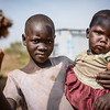 """Nadia holding her little sister Salama (2). They fled from Yei in South Sudan in October 2016 together with their family and are currently living in Bidibidi in Uganda. <br /> <br /> Quotes from Nadia: """"It is okay staying here. We are free and allowed to walk around and I do not feel afraid. It is safe here."""" <br /> <br /> Bidibidi settlement in northern Uganda was established in August 2016 and has quickly become one of the world's largest refugee settlements. By January 2017 it was housing more than 270,000 refugees from South Sudan - and had reached its full capacity. NRC is providing water and sanitation services in the settlement. <br /> <br /> In total, Uganda is currently home to about 600,000 refugees from South Sudan. <br /> <br /> Photo: NRC/Tiril Skarstein"""