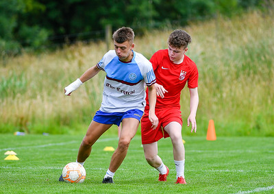 Tommy Dixon makes a run up the wing as Stephen Carson closes in.  Photo by Ronan McGrade