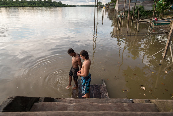 """Marlon Langeland and Nilson is testing the the temperature in the water.<br /> <br /> Nilson, a 22 year old boy survived a massacre in his village. After the massacre he and his family had to flee. Unfortunately, one of his brothers and three male cousins where killed in the massacre. <br /> <br /> Nilson grew up in a small village along the river in the region of Chocó, Colombia. He loved playing games, go swimming and fishing with his friends. He was studying at school and life was good. His dream got tossed when the community repetitively was threatened and they eventually had to flee. <br /> <br /> The massacre<br /> It was an ordinary day in March 2017. The women of the village were celebration women's day. Nilson and many other males in the small village was doing their daily activities including fishing, playing and walking around when all of a sudden an armed group attacked. """"Suddenly people that we had never seen before appeared. They were armed and attacked everyone they came across. They looked angry. They did not speak with anyone; they just stared at people in silence and killed everyone they caught"""". Five male youth got killed.<br /> <br /> Today, the village is abandon and appears more like a ghost town. Nilson and his family are now too afraid to return to their village because of the uncertainty that follows and if another massacre will happen again.<br /> <br /> Life today<br /> Nilson has now problems with adapting to his new life after the massacre and loss of his brother and three cousins and he has lost his desire to do things he used to like. """"Things are not the same. Things that I used to do there I now avoid doing here. Sometimes I do not feel well, I feel uncomfortable, because of the things that have changed so much"""". He has stopped studying and many of his old friends and relatives have moved elsewhere. <br /> <br /> Despite all this, he feels safe in the village they are displaced and now trying to adapt their new life. """"I am overcoming """