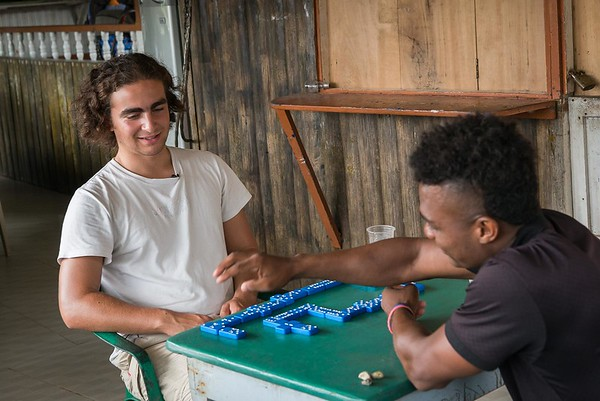"""Nilson is teaching Marlon Langeland how to play Domino.<br /> <br /> Nilson, a 22 year old boy survived a massacre in his village. After the massacre he and his family had to flee. Unfortunately, one of his brothers and three male cousins where killed in the massacre. <br /> <br /> Nilson grew up in a small village along the river in the region of Chocó, Colombia. He loved playing games, go swimming and fishing with his friends. He was studying at school and life was good. His dream got tossed when the community repetitively was threatened and they eventually had to flee. <br /> <br /> The massacre<br /> It was an ordinary day in March 2017. The women of the village were celebration women's day. Nilson and many other males in the small village was doing their daily activities including fishing, playing and walking around when all of a sudden an armed group attacked. """"Suddenly people that we had never seen before appeared. They were armed and attacked everyone they came across. They looked angry. They did not speak with anyone; they just stared at people in silence and killed everyone they caught"""". Five male youth got killed.<br /> <br /> Today, the village is abandon and appears more like a ghost town. Nilson and his family are now too afraid to return to their village because of the uncertainty that follows and if another massacre will happen again.<br /> <br /> Life today<br /> Nilson has now problems with adapting to his new life after the massacre and loss of his brother and three cousins and he has lost his desire to do things he used to like. """"Things are not the same. Things that I used to do there I now avoid doing here. Sometimes I do not feel well, I feel uncomfortable, because of the things that have changed so much"""". He has stopped studying and many of his old friends and relatives have moved elsewhere. <br /> <br /> Despite all this, he feels safe in the village they are displaced and now trying to adapt their new life. """"I am overcoming some things and I"""
