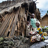 1. DR Congo - Noella and her children before their damaged hut in Kishanga camp