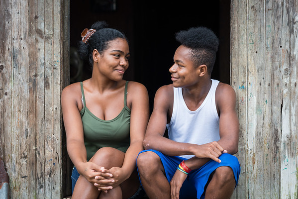 """Leidy Tatiana and her little brother Ferney, 16. He was shot in the arm during the armed attack, but he managed to escape.<br /> <br /> Leidy Tatiana, a 20 years old girl and her family had to flee after an armed attack in her village which is situated along one of many rivers in the region of Chocó, Colombia. Her oldest brother got killed in this attack as well as as three cousins and an uncle. All male youth. Her life was changed when she, her family and and her community had to flee.<br /> <br /> Armed attack<br /> It was an ordinary day in March 2017 when Leidy Tatiana and other women where celebrating women's day. The remaining village, mostly males, continued their normal activities when all of a sudden an armed group attacked. The women couldn't go back home that night. <br /> <br /> In addition to her brother and uncle that got killed her youngest brother, Ferney, a 14-year old boy, was shot but fortunately survived. He was standing on a pier when an armed man asked him for his phone. He was shot in his arm and fell off the pier and into the water. He was forced to swim for his life while the armed man continued to fire bullet on him. Ferney even witnessed his own brother and his cousin being killed while saving his own. <br /> <br /> Today, the village is abandon and appears more like a ghost town. Leidy Tatiana and her family are now too afraid to return to their village because of the uncertainty that follows and if another armed attack will happen again. <br /> <br /> The future<br /> Sometimes """"I feel as if I'm missing something: my land, my town, my home. Sometimes I want to go back, but I have very painful memories and that is the reason I avoid it. I feel very afraid. Just seeing the place where my brother and my uncle died, I just can't do it"""", Leidy Tatiana explains.<br /> <br /> Sometimes she feels positive and at times not at all. Sometimes she goes out and do what she feels like doing, other times not. She feels scared and the armed attack prohi"""