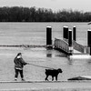 The boarding dock at English Park is cut off from access to land due to the high level of the Ohio River as Karen Crowe walks her dog, Jaxx, along the walkway in the park on Tuesday, Feb. 20, 2018, in Owensboro, Ky. (Greg Eans/The Messenger-Inquirer via AP)