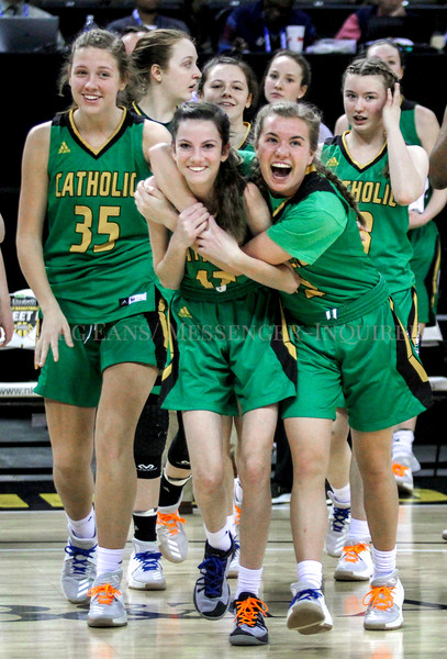 Photo by Greg Eans, Messenger-Inquirer.com | geans@messenger-inquirer.com<br /> <br /> Owensboro Catholic's Catherine Head, right, hugs teammate Caroline Kanipe, middle, as they celebrate with Ally Maggard, left, and other team members after beating Johnson Central 56-46 during the first round of the 2018 St.Elizabeth Healthcare/KHSAA Girls Sweet Sixteen tournament at BB&T Arena in Highland Heights.
