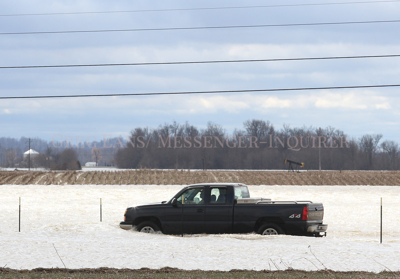 Photo by Greg Eans, Messenger-Inquirer.com | geans@messenger-inquirer.com<br /> <br /> A driver in a pickup truck maneuvers through flood water covering U. S. 60 near Stanley. Numerous roads in the county are still closed due to the flooding.