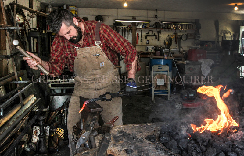 Photo by Greg Eans, Messenger-Inquirer.com | geans@messenger-inquirer.com<br /> <br /> Martin Millay uses a hammer and an anvil while working to forge a piece of mild steel into a bottle opener in his blacksmith shop at his home in Whitesville.