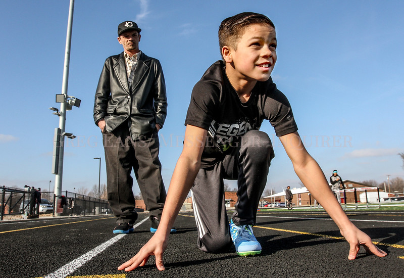 Photo by Greg Eans, Messenger-Inquirer.com   geans@messenger-inquirer.com<br /> <br /> King Combest, 10, gets some coaching from his father, Casey Combest, during a workout at the Owensboro Middle School track.