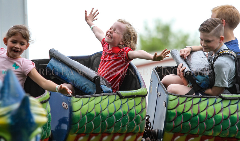 Charlie Reeves, 7, holds out his arms while riding the Dragon Wagon amusement ride with friends Sophia Cadiz, 6, left, Logan Wood, 10, right, and his brother William Reeves, 10, background right, at the 55th annual Tamarack Carnival on Friday, May 4, 2018, in Owensboro, Ky. (Greg Eans/The Messenger-Inquirer via AP)