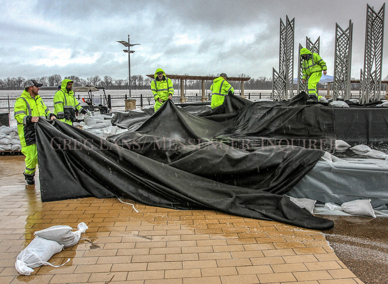 A Facilities Maintenance crew from Owensboro Public Works uses sandbags to secure sheets of fabric tarp over the main fountain at Smothers Park, preparing for possible flooding in the park from the Ohio River on Friday, Feb. 23, 2018, in Owensboro, Ky. (Greg Eans/The Messenger-Inquirer via AP)