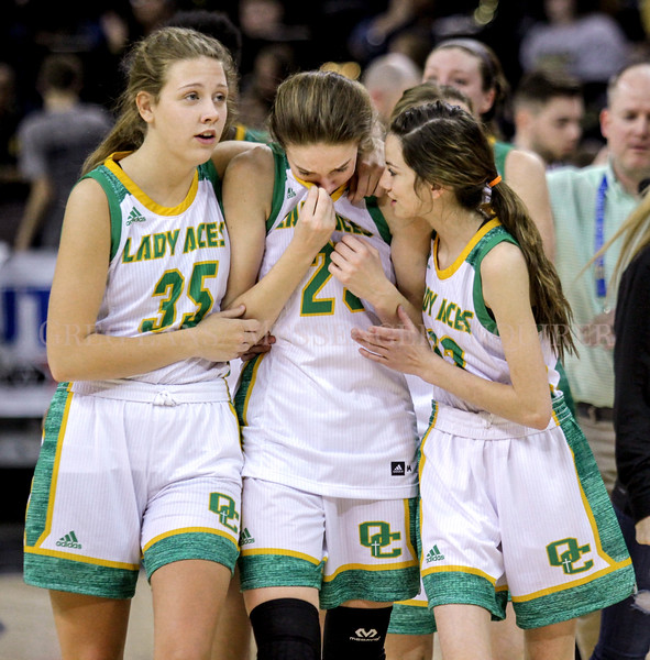 Owensboro Catholic's Madelyn Lyon, center, is consoled by teammates Caroline Kanipe, right, and Ally Maggard, left, as they walk off of the court after a 67-66 loss to Mercer County on Friday, March 9, 2018, during the quarter finals of the 2018 St.Elizabeth Healthcare/KHSAA Girls' Sweet Sixteen tournament at BB&T Arena in Highland Heights, Ky. (Greg Eans/The Messenger-Inquirer via AP)