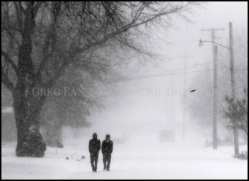 Photo by Greg Eans, Messenger-Inquirer.com/geans@messenger-inquirer.com<br /> <br /> Neighborhood friends Jesse Henning, left, and Justin Ward walk along York Street as snow falls around them and a bird flies by. The two were enjoying a day off from school due to the weather.
