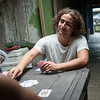 Marlon Langeland is teaching Jhoana a card game.<br /> <br /> Jhoana, 20 years old, and her family had to flee after an armed attack in her village. Two of her brothers and her two cousins where killed. All male youth.<br /> <br /> Jhoana grew up in a small village along the river in the region of Chocó, Colombia. She loved playing with her siblings and cousins, walking in the bush and went swimming. Her dream was to study veterinarian because her passion for animals. Her dream got tossed when the community repetitively was threatened and they eventually had to flee.<br /> <br /> Armed attack<br /> It was an ordinary day in March 2017 when Jhoana and other women were celebrating women's day. The remaining village, mostly males, continued their normal activities when all of a sudden an armed group attacked. That night Jhoana couldn't sleep due to nightmares and not knowing the extent of the attack and not being able to go back to the village before the next day.<br /> <br /> The next day they witnessed several dead and wounded youths and she was devastated. Not one, but two of her elderly brothers had lost their lives. One where tied up and the other one was laying dead on a rooftop with rain poring down on the body. Furthermore, two cousins and a family friend, all young, and all males also lost their life's. <br /> <br /> Today, the village is abandon and appears more like a ghost town. Jhoana and her family are now too afraid to return to their village because of the uncertainty that follows and if another armed attack will happen again.<br /> <br /> Life today<br /> Now, her daily activities are restricted to short trips; when she leaves the house, she does not go far and she coordinates her trips with relatives. A common daily activity can consist of meeting her cousins at the pier and watch them swim. Or, she will only hang out in their house. At home, where she spends most of her time, she writes her diary to cope with the armed attack and the loss of her two 