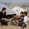 Rebecca Dibb talking to three young boys in Domiz Refugee Camp for Syrian refugees in Iraq. Photo Credit: NRC/Ingrid Prestetun