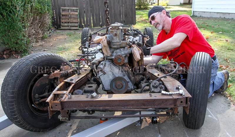 """Photo by Greg Eans, Messenger-Inquirer.com/geans@messenger-inquirer.com<br /> <br /> Jeff Harmon works at removing the engine from the chassis of a 1966 Datsun Roadster in his driveway on Griffith Avenue in Owensboro, Ky.  Harmon is restoring two Datsun Roadsters from the parts of three of the cars. """"It's a beautiful day to get some work done,"""" Harmon said."""