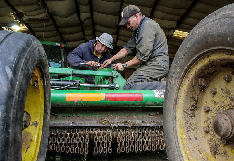 Photo by Greg Eans, Messenger-Inquirer.com/geans@messenger-inquirer.com<br /> <br /> Armando Olague. left, and Axel Gomez Castello work inside the shop at Keugel Farms on Worthington Road, replacing a gear on a bush hog that is leaking oil. Once the repair is finished, they'll start mowing cow pastures and trimming farmland for the upcoming farming season.