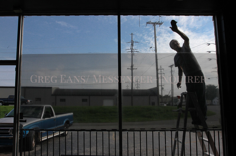Photo by Greg Eans, Messenger-Inquirer.com/geans@messenger-inquirer.com<br /> <br /> Robert Vincent works on a ladder to remove tinting from a window of a building on W. 4th Street Owensboro, Ky. He was helping a friend out with the project to prepare the building to be rented.