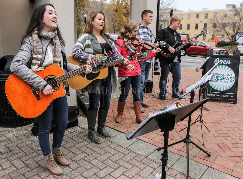 Photo by Greg Eans, Messenger-Inquirer.com/geans@messenger-inquirer.com<br /> <br /> Hayley Payne, from left, Skylar Lanham, Grace Brocato, Seth Pence and Tyler Brown, members of the bluegrass, gospel and country group Gaining Ground, perform on the sidewalk in from of the International Bluegrass Music Museum during downtown Owensboro's Holiday Stroll.