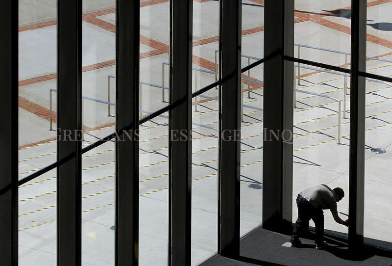Photo by Greg Eans, Messenger-Inquirer.com/geans@messenger-inquirer.com<br /> <br /> Owensboro Convention Center employee Jon York works in the main lobby of the building, cleaning windows for an upcoming event.