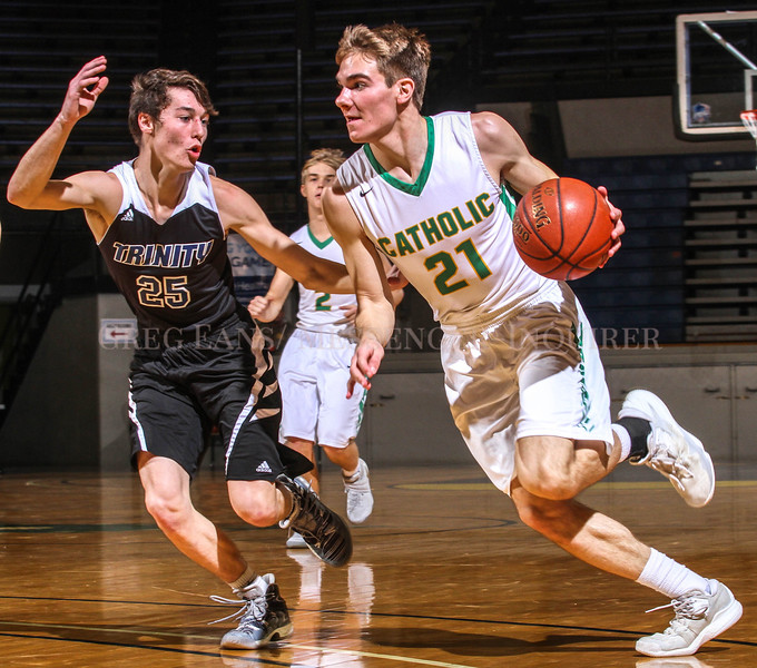 Photo by Greg Eans, Messenger-Inquirer.com/geans@messenger-inquirer.com<br /> <br /> Owensboro Catholic's Luke Hayden drives past Whitesville Trinity's Eric Howard during action at the Owensboro Sportscenter.