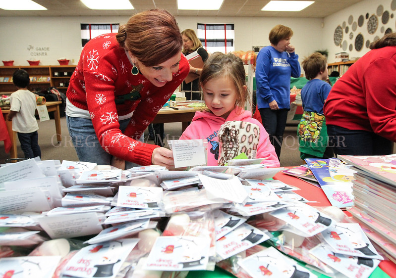 "Photo by Greg Eans, Messenger-Inquirer.com/geans@messenger-inquirer.com<br /> <br /> Heather Thomas, left, a school social worker at Foust Elementary School, helps kindergarten student Lynax Halladay pick out a ""Snowman Soup"" in the school's Christmas Store. Students at the school shopped in the store for gifts for their families and friends by spending ""Foust Bucks"" that they have earned throughout the year."