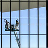 Photo by Greg Eans, Messenger-Inquirer.com/geans@messenger-inquirer.com<br /> <br /> Tad Bunker, left, and Derek Masterson, with Clear Service Solutions out of Evansville, use a lift to clean the windows on the outside front of the Owensboro Convention Center.
