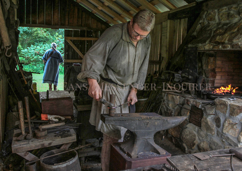 """Photo by Greg Eans, Messenger-Inquirer.com/geans@messenger-inquirer.com<br /> <br /> Jeff Helm of Hartford uses an anvil and hammer to forge an """"S"""" hook out of a steel bar during a demonstration for Pioneer Days at the James Lambert Pioneer Village at Yellow Creek Park. The hook could be used to hang a kettle over a hot fire for cooking in the pioneer days."""