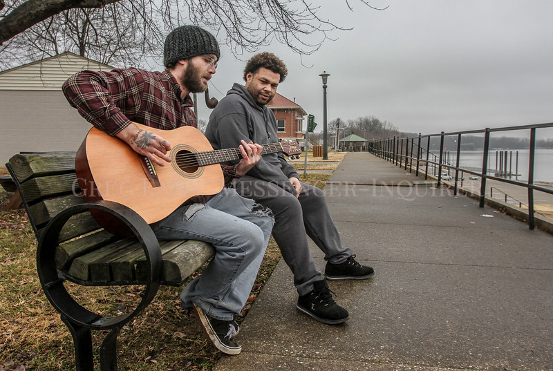 Joseph Carter, left, plays an acoustic guitar as his friend, Rob Hill, looks on as the two sit on a bench at English Park on Tuesday, Jan. 9, 2017, in Owensboro, Ky. The two were taking advantage of the warmer outside temperatures and the scenery in the park along the Ohio River. (Greg Eans/The Messenger-Inquirer via AP)