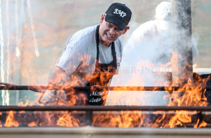 Photo by Greg Eans, Messenger-Inquirer.com/geans@messenger-inquirer.com<br /> <br /> John Mattingly with the Blessed Mother cooking team stirs coals in one of the team's Bar-B-Q pits while cooking during the 39th annual International Bar-B-Q Festival in Owensboro, Ky.