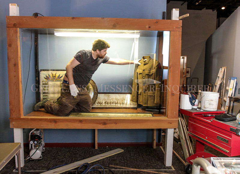 "Photo by Greg Eans, Messenger-Inquirer.com/geans@messenger-inquirer.com<br /> <br /> Ben Atherton, assistant curator at the Owensboro Museum of Science & History, places a WWI uniform in a display case while working to install the ""World War I and America"" exhibit at the museum. The temporary exhibit opens April 1 and runs through November 11 on the first floor of the museum and is sponsored by a grant received from the Library of America in partnership with the Gilder Lehrman Institute of American History and the National Endowment for the Humanities. Patrons at the library will be able to walk through a WWI trench and learn what life was like for soldiers and how Owensboro helped with the war effort."