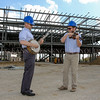 "Chris Joslin, left, executive director of the International Bluegrass Music Museum, and Danny Clark, the museum's membership and special events manager, don hard hats and play a few bluegrass tunes on the banjo and fiddle at the construction site of the new museum at Frederica and West Second Street on Tuesday, April 4, 2017, in Owensboro, Ky.  The two were celebrating the restart of construction on the building, which was idled by the bankruptcy of general contractor Peyronnin Construction Company. Danco Construction Company of Evansville, In., and Owensboro, Ky., have taken charge as the replacement contractor and the museum is slated to open in the spring of 2018. ""This is the very first jam session at the new bluegrass museum,"" Joslin said. (Greg Eans/The Messenger-Inquirer via AP) MANDATORY CREDIT"