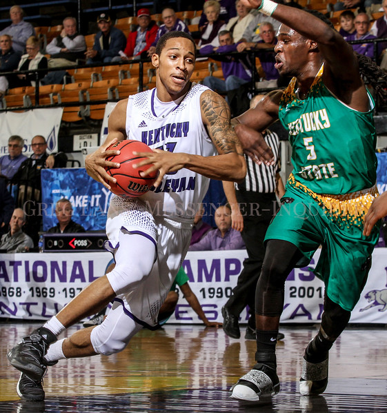 Photo by Greg Eans, Messenger-Inquirer.com/geans@messenger-inquirer.com<br /> <br /> Kentucky Wesleyan's Adam Stanford gets past Kentucky State's Reggie Breeden for a shot in the lane during a college basketball game at the Owensboro Sportscenter in Owensboro, Ky.