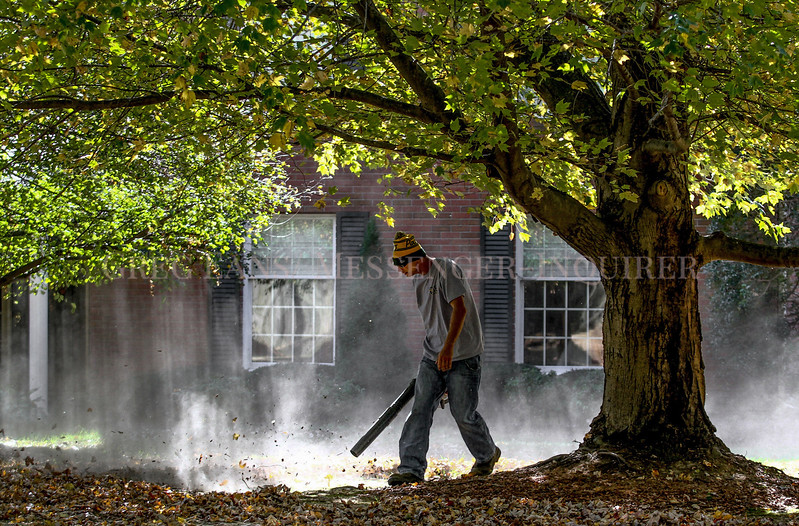 Photo by Greg Eans, Messenger-Inquirer.com/geans@messenger-inquirer.com<br /> <br /> Ben Payne with Elite Lawn Care uses a leaf blower to clean up an area around a large tree while working on lawn maintenance at Quail Ridge Condominiums.