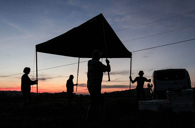 Photo by Greg Eans, Messenger-Inquirer.com/geans@messenger-inquirer.com<br /> <br /> Laura Flowers, from left, Walt Baldwin, Jay Burdick and Jordan Ellis, from Frankfort, Ky, team together to set up their canopy tent on Monday morning at Orchardale Farm in the town of Cerulean, near Hopkinsville. The four friends arrived early in the morning to  prepare their spot at the farm for viewing the total solar eclipse.