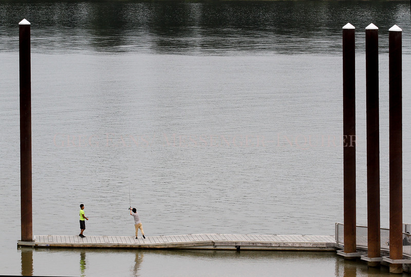 """Photo by Greg Eans, Messenger-Inquirer.com/geans@messenger-inquirer.com<br /> <br /> Willie Barrera, 13, casts a line out into the Ohio River while fishing with his brother, Erik, 18, left, at English Park. The two had just come to town from Florida with other family members to work at harvesting vegetables in Daviess County. """"We're getting some fishing in while we can,"""" Erik Barrera said. """"We start tomorrow and won't have a break for about a month."""""""