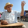 "Photo by Greg Eans, Messenger-Inquirer.com/geans@messenger-inquirer.com<br /> <br /> Joe Offerman waves to passing people as he carves a shelf mouse at a booth he has set up at the Reid's Orchard Apple Festival. ""I've been woodcarving at the festival for 30 years,"" he said."