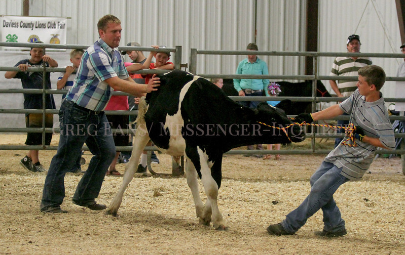 Photo by Greg Eans, Messenger-Inquirer.com/geans@messenger-inquirer.com<br /> <br /> Michael Baird, a cattle show ringman, left, helps Dakota Fry, 12, of Philpot handle his holstein steer, Pops, during the intermediate showmanship competition in the Tom Curtsinger Agricultural Education Center during the Daviess County Lions Club Fair.