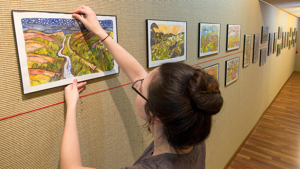 Katy Guthrie hangs a watercolor painting by Robert Joy in preparation for the art exhibition titled, Rare Vision, Thursday at Garden City Arts. The reception for the show will be at 7 p.m. today. Joy is an Ellsworth-based artist specializing in mixing sharpie and watercolor mediums.