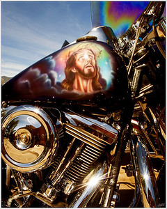 """Harley 3:16"" I came around the corner in Taos, NM and there he was, Jesus, staring up at me from the gas tank of this chromed out Harley.  The star bursts painted in the celestial heavens around Jesus' head were fixed in place by the original artist; the one in the middle of his brow, however, was actually the sun's reflection. I didn't catch the unfortunate placement  until after I was back to Atlanta."
