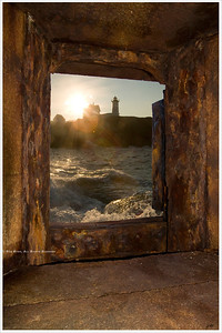 """View of Nubble Light... from Fort Preble - 45 minutes away"" a composite made of two images from two locations along Maine's coastal shore. The rusting battalion window encased in the thick granite walls of Fort Preble provided a perfect nautical frame for this view of Nubble Light at sunrise.  For more information, visit: http://www.portlandharbormuseum.org/"